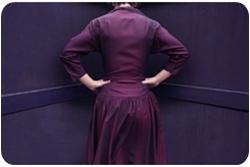 Женщина в фиолетовом платье стоит в углу