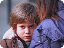 Грустный мальчик смотрит из-за плеча матери