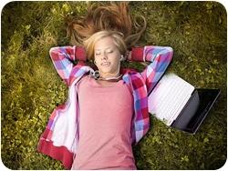 Девушка с нетбуком лежит на поляне