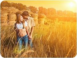 Молодая пара обнимается на лугу
