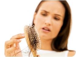Женщина смотрит на волосы, оставшиеся на расчёске